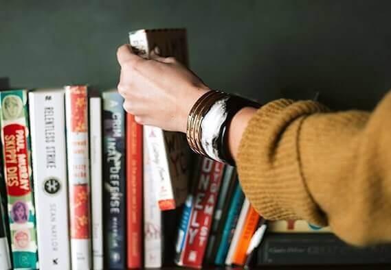 Frau greift in ein Bücherregal