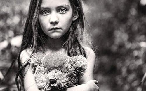Ein Mädchen klammert sich vor Schmerzen an ihren Teddy.