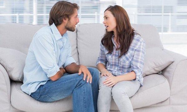 Paar spricht auf dem Sofa über Beziehungsprobleme.