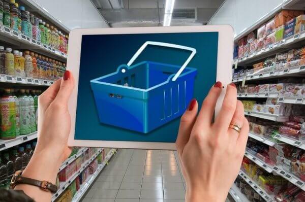 Eine Frau hält ein Tablet in einem Supermarkt hoch und der Tablet-Screen zeigt einen leeren Einkaufskorb.