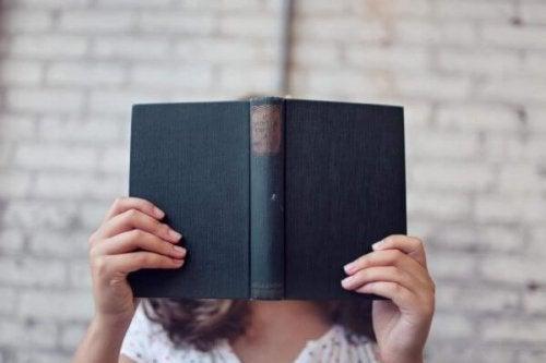 Frau, die ihr Gesicht mit einem Buch verdeckt
