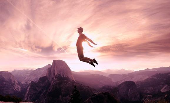 Mann, der über Berge springt