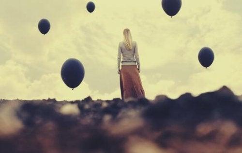 Eine blonde Frau steht auf einem Feld und ist von dunklen Luftballons umgeben.