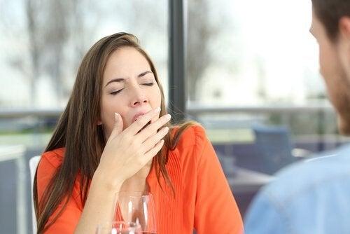 Eine Frau gähnt, während sie beim Mittagessen ist.