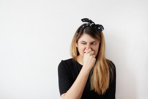 Eine junge Frau hält sich die Nase zu.