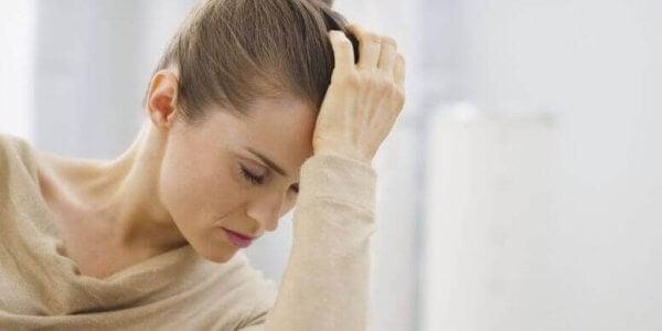 Eine nachdenkliche junge Frau hat ihren Kopf auf ihre Hand gestützt.