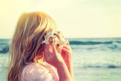 Eine Frau lauscht dem Meeresrauschen in einer Muschel.