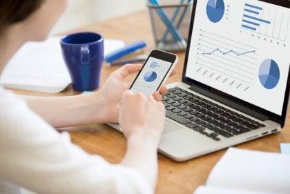 Eine Frau sitzt vor ihrem Laptop und sieht sich Statistiken an.