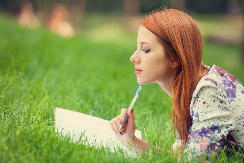 Frau liegt auf einer Wiese und schreibt
