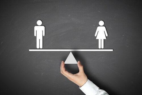 Ein Tafelbild, das eine Figur eines Mannes und einer Frau ausbalanciert auf einer Waage zeigt.