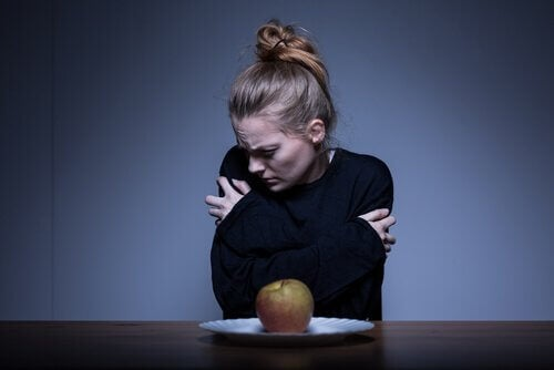 Frau mit unangemessenem Körperbild vor Apfel