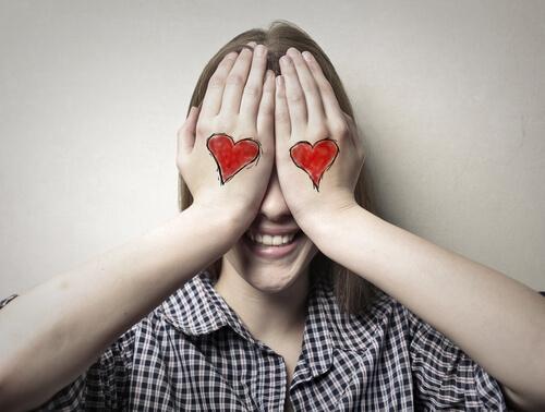 Frau mit aufgemalten Herzen auf ihren Händen hält sich die Augen zu