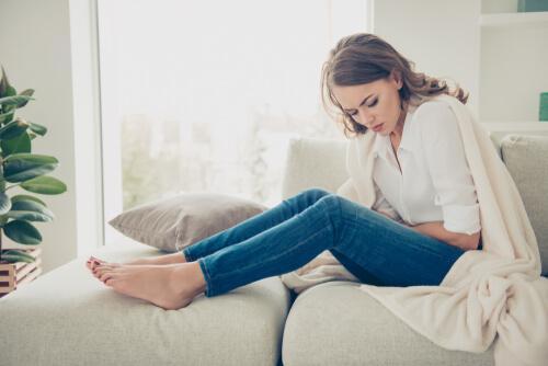 Frau sitzt mit Bauchschmerzen auf der Couch