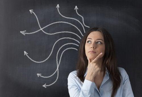 Eine Frau denkt nach, während sie vor einer Tafel steht, auf der Pfeile aufgemalt sind.