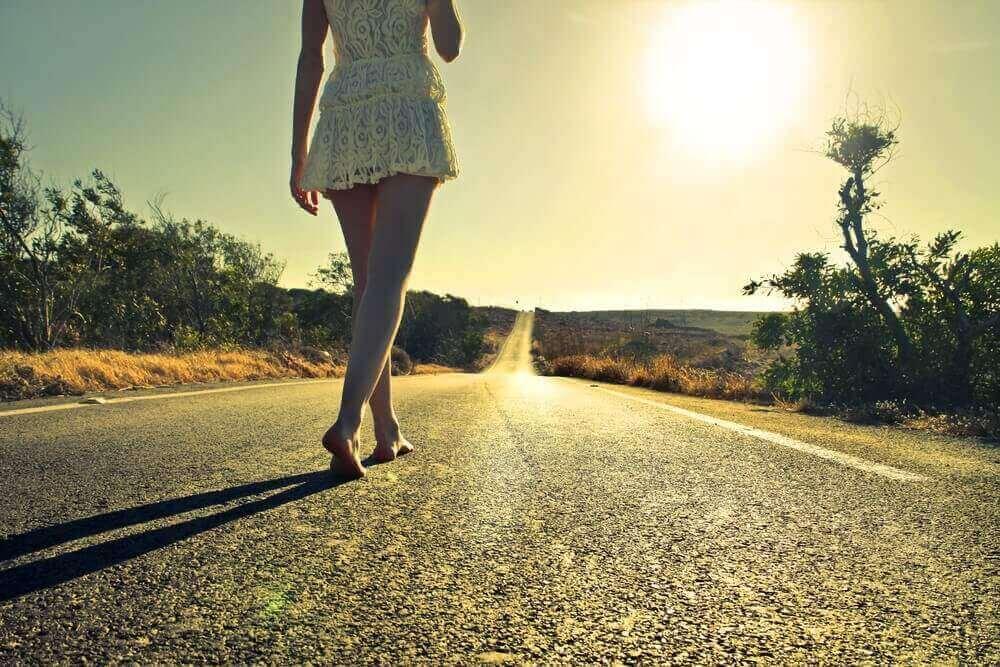 Frau spaziert ohne Schuhe eine Straße entlang