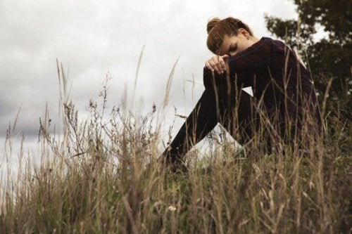 Eine junge Frau sitzt traurig an einem Flussufer und hat ihren Kopf auf die Knie gelegt.