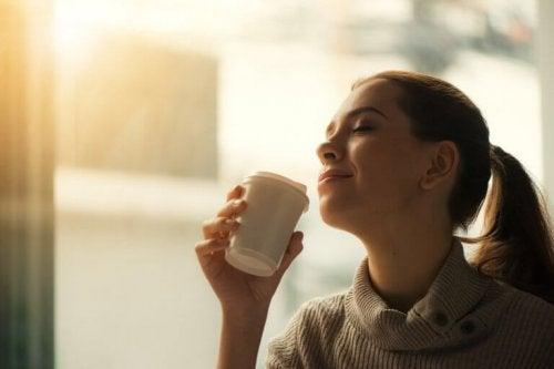 Frau mit geschlossenen Augen genießt einen Kaffee