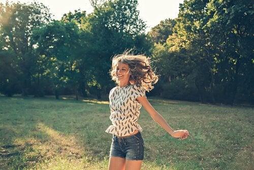 Glückliche Frau auf einer Wiese setzt ein Zeichen gegen die Angst vor dem Glücklichsein