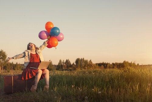 Glückliche Frau, die im Hier und Jetzt lebt, hält Ballons in der Hand