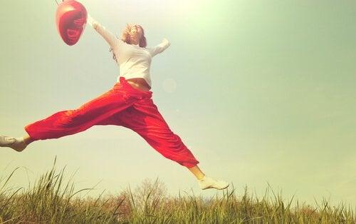 Eine Frau ist mutig und springt vor Freude in die Luft.