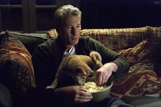 Eine Filmszene, in der ein Welpe auf dem Schoss des Schauspielers Richard Geres sitzt.