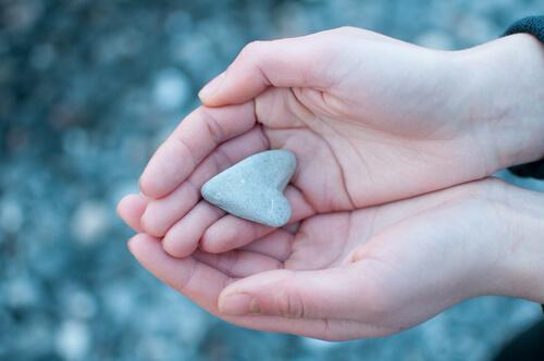 Hände, die einen Stein in Herzform halten