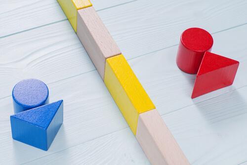 Eine blaue und rote Holzfigur, die durch Bauklötze getrennt sind.