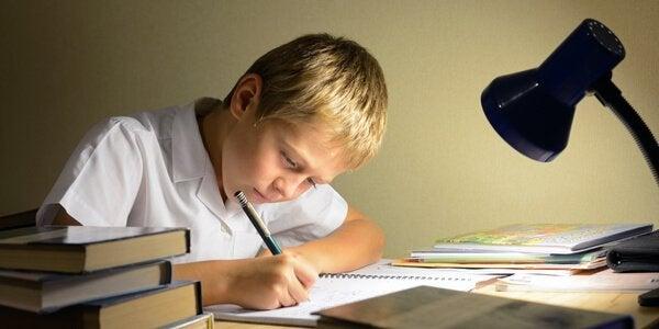 Ein Junge sitzt an seinen Hausaufgaben im Schein einer Schreibtischlampe.