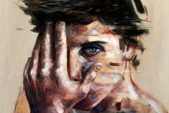 Junger Mann hält sich seine Hand vors Gesicht
