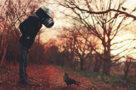 Mann mit einer Kamera als Kopf schaut auf einen Vogel