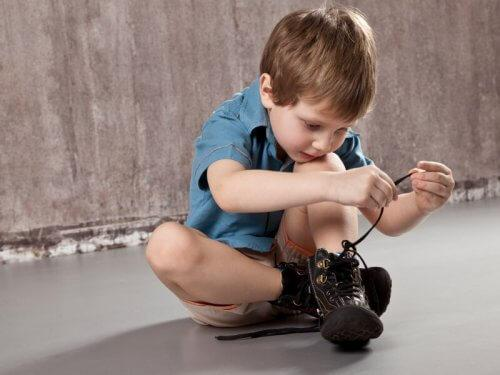 Junge versucht, seine Schnürsenkel zuzubinden