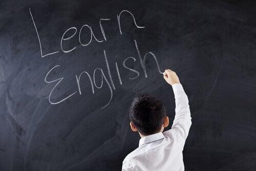 """Ein Junge schreibt """"Learn English"""" an die Tafel."""