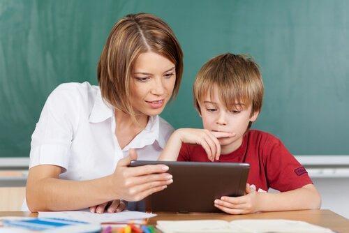 Lehrerin zeigt Schüler etwas auf einem Tablet