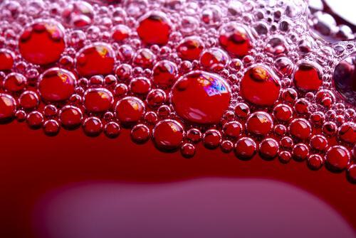Nahaufnahme von Blubberbläschen in einer roten Limonade
