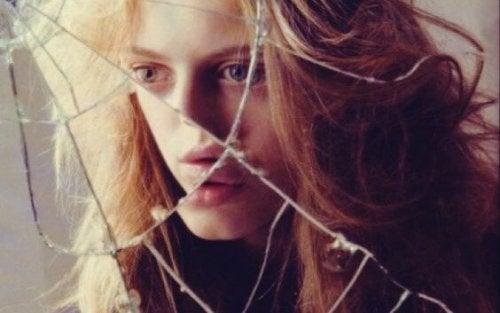 Ein Mädchen betrachtet sich in einem zerbrochenen Spiegel.