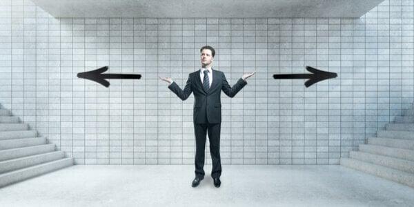 Ein Mann steht an einem Scheideweg und fragt sich, welche Richtung er einschlagen soll.