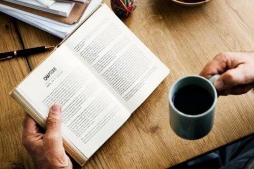 Mann mit Kaffeetasse liest Buch