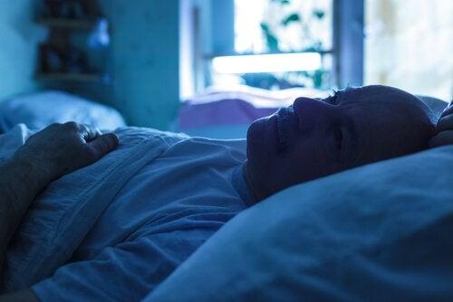 Mann, der im Bett liegt und sich Sorgen macht