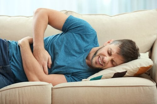 Mann liegt mit Bauchschmerzen auf dem Sofa.