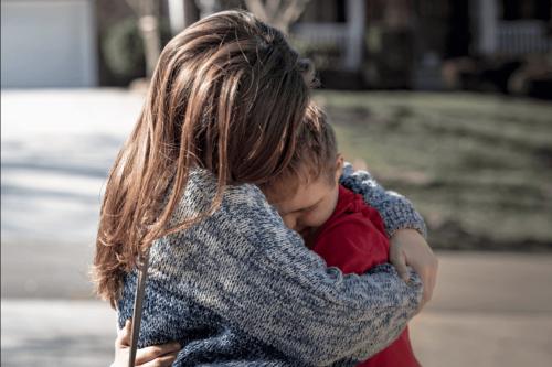 Eine Mutter umarmt ihr behindertes Kind.