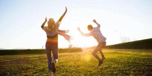 Paar springt durchs Feld