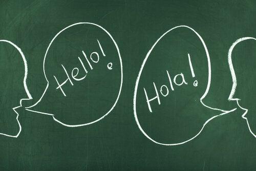 Zwei mit Kreide gemalte Sprechblasen zeigen die Wörter Hello und Hola.