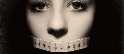 Stoppt Anorexie - Frau mit Maßband vor dem Mund