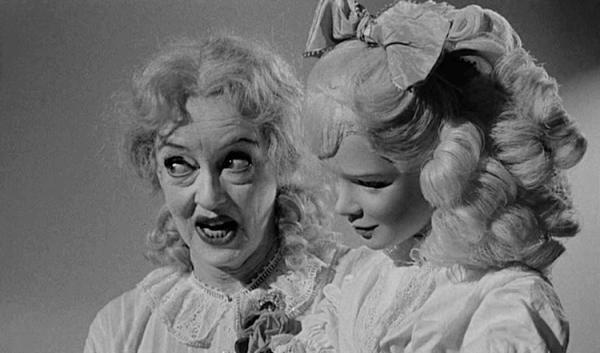 Filmszene aus Baby Jane, die Bette Davis mit einer Puppe zeigt