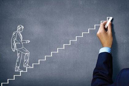 Eine Hand, die ein Tafelbild malt, das einen Mann eine Treppe hinaufsteigen zeigt.