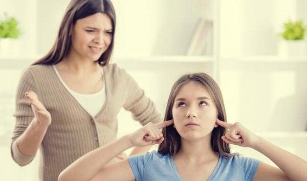 Ein Teenager steckt sich die Finger in die Ohren, während seine Mutter mit ihm schimpft.