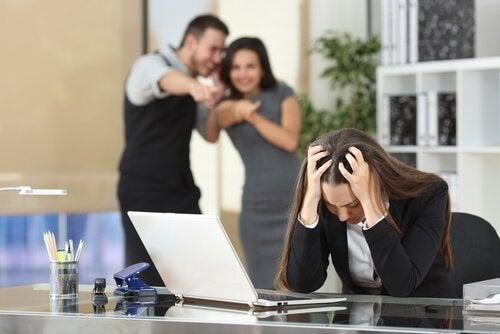Eine Frau wird von ihren toxischen Kollegen gemobbt.