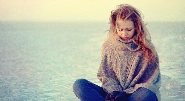 Ein Mädchen sitzt traurig und in Gedanken versunken am Meer.