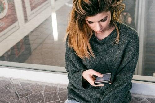 Traurige Frau wartet auf einen Anruf, symptomatisch für Angst und Stress bei der Arbeitssuche