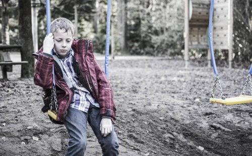 Ein ausgegrenzter und gemobbter Junge sitzt mutlos auf einer Schaukel.